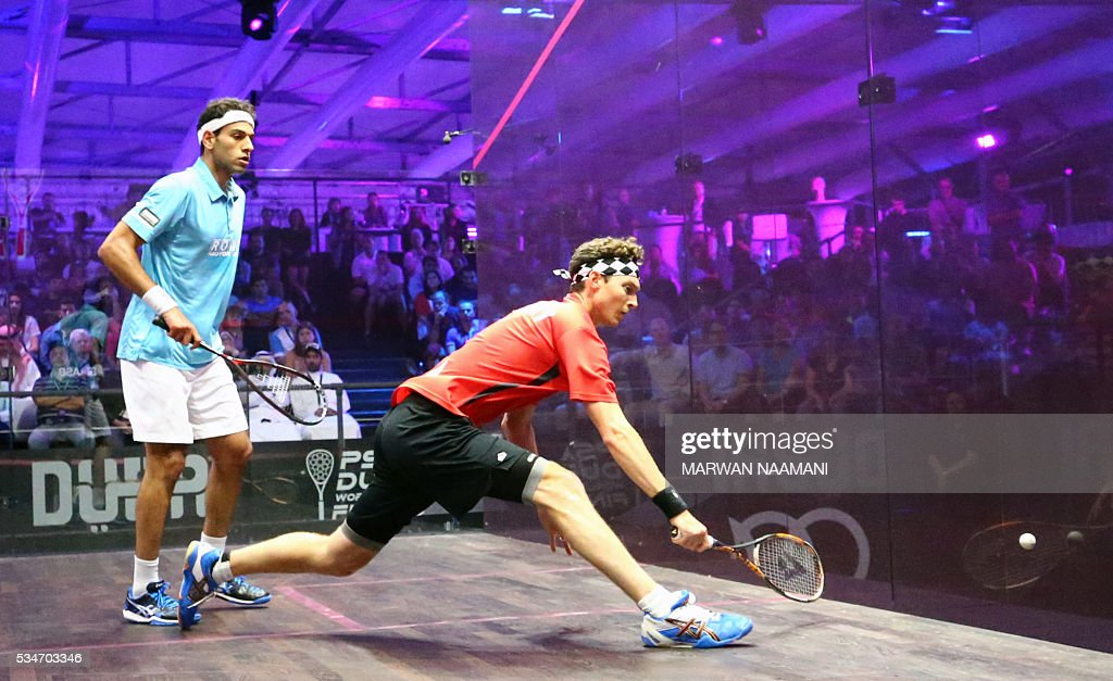 Cameron Pilley of Australia (R) plays a backhand to Mohamed El Shorbagy of Egypt during their semi-final match of the Dubai PSA World Series Finals squash tournament in Dubai on May 27, 2016. / AFP / MARWAN