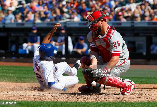 Cameron Rupp of the Philadelphia Phillies can't come up with the ball as Dominic Smith of the New York Mets scores a run in the fourth inning at Citi...