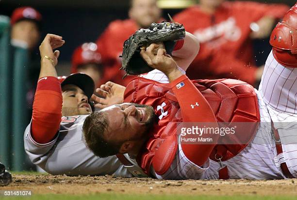 Cameron Rupp of the Philadelphia Phillies tags out Eugenio Suarez of the Cincinnati Reds during a collision at home plate in the ninth inning during...