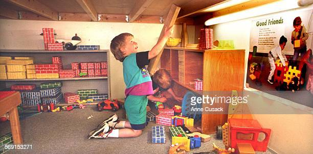 Cameron Saier age 4 helps his friend Michael McVey age 3 put the blocks away at Roots and Wings Child Care Center in TO
