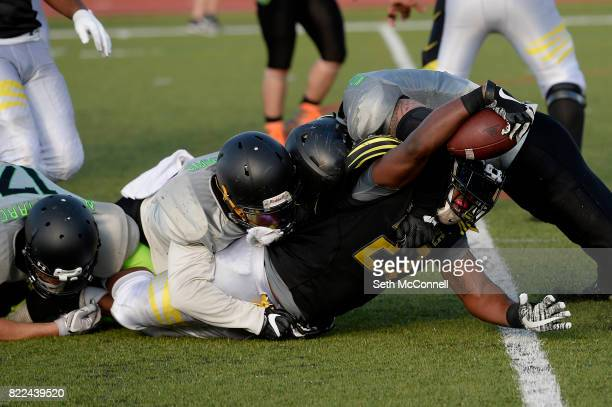 Cameron Smith is brought down by the NoCo Nightmare as he reaches for more yardage during the second quarter at North Stadium on July 22 in...