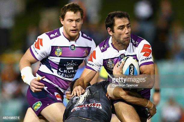 Cameron Smith of the Storm is tackled during the round 21 NRL match between the Wests Tigers and the Melbourne Storm at Leichhardt Oval on July 31...