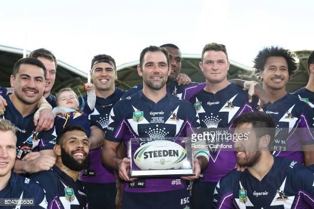 Cameron Smith of the Storm poses with his team mates after he played his 350th match during the round 21 NRL match between the Melbourne Storm and...