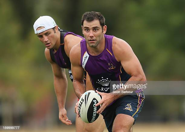 Cameron Smith of the Storm runs with the ball as Cooper Cronk looks on during a Melbourne Storm NRL training session at Gosch's Paddock on January 25...