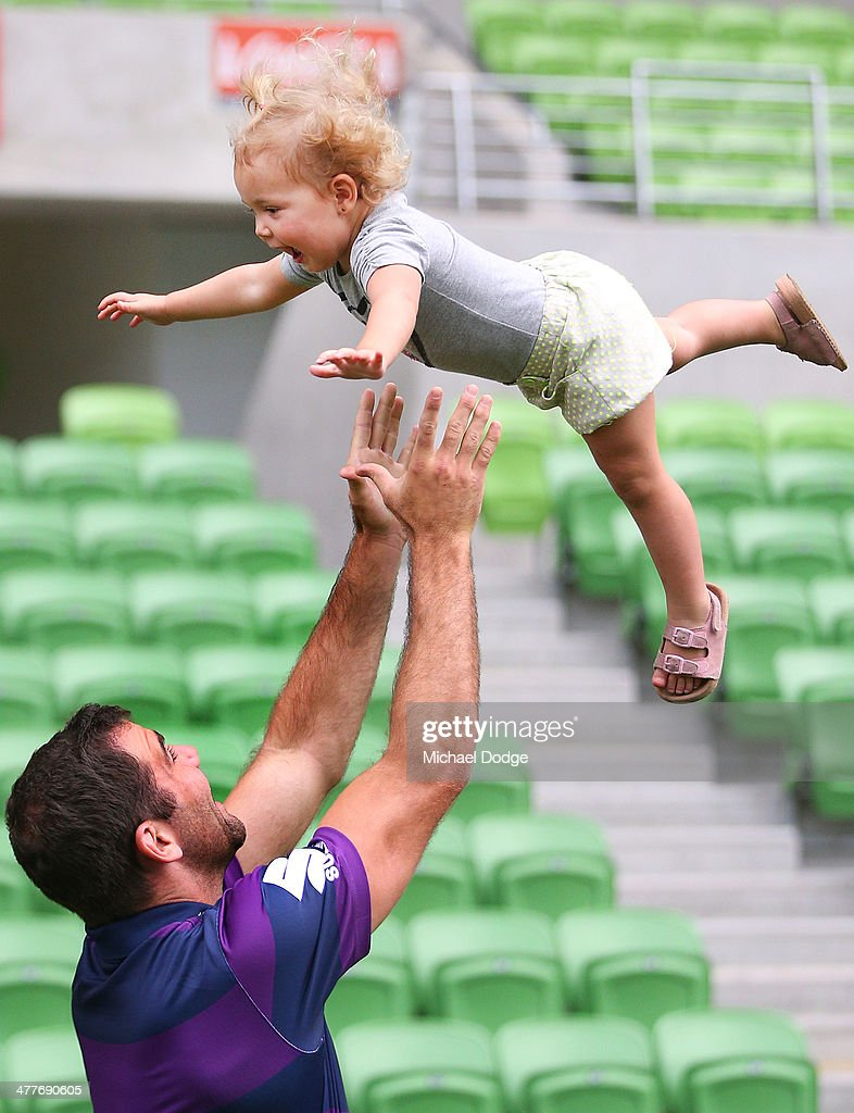 Cameron Smith of the Storm, who has signed a four year contract extension and breaks the game record for a Storm player this weekend, throws up daughter Matilda , 20 months during a Melbourne Storm NRL media session at AAMI Park on March 11, 2014 in Melbourne, Australia.