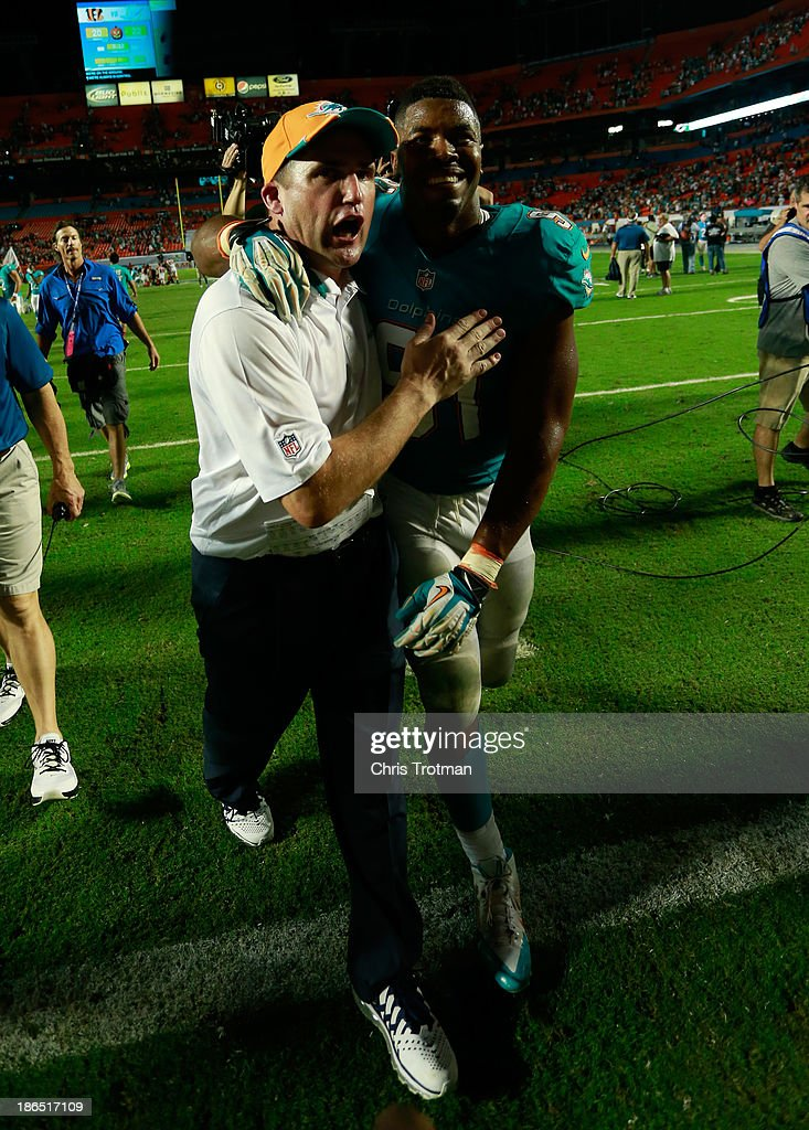 Cameron Wake #91 (R) of the Miami Dolphins is congratulated by a coach as he leaves the game following his teams victory over the Cincinnati Bengals at Sun Life Stadium on October 31, 2013 in Miami Gardens, Florida.