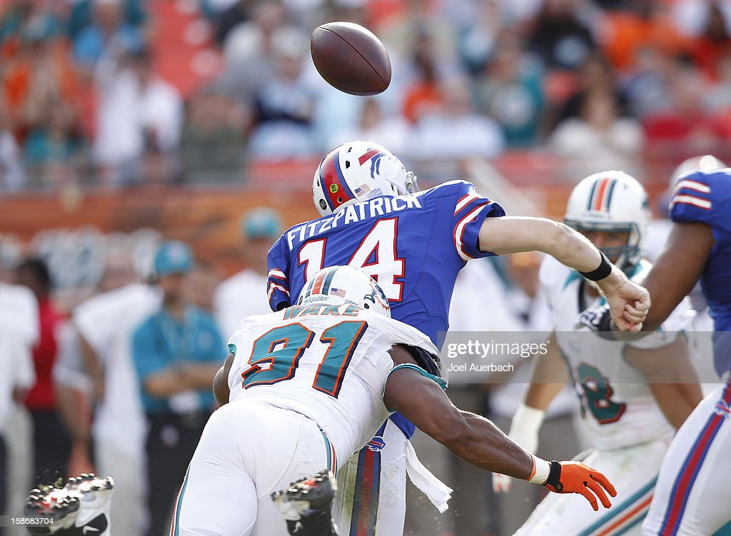 <a gi-track='captionPersonalityLinkClicked' href=/galleries/search?phrase=Cameron+Wake&family=editorial&specificpeople=2330195 ng-click='$event.stopPropagation()'>Cameron Wake</a> #91 of the Miami Dolphins knocks the ball out of the hand of <a gi-track='captionPersonalityLinkClicked' href=/galleries/search?phrase=Ryan+Fitzpatrick&family=editorial&specificpeople=622098 ng-click='$event.stopPropagation()'>Ryan Fitzpatrick</a> #14 of the Buffalo Bills as he sacks him on December 23, 2012 at Sun Life Stadium in Miami Gardens, Florida. The Dolphins defeated the Bills 24-10.
