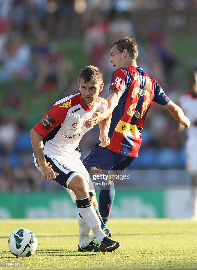 Cameron Watson of Adelaide contests the ball with Ryan Griffiths of the Jets during the round 15 A-League match between the Newcastle Jets and Adelaide United at Hunter Stadium on January 5, 2013 in Newcastle, Australia.