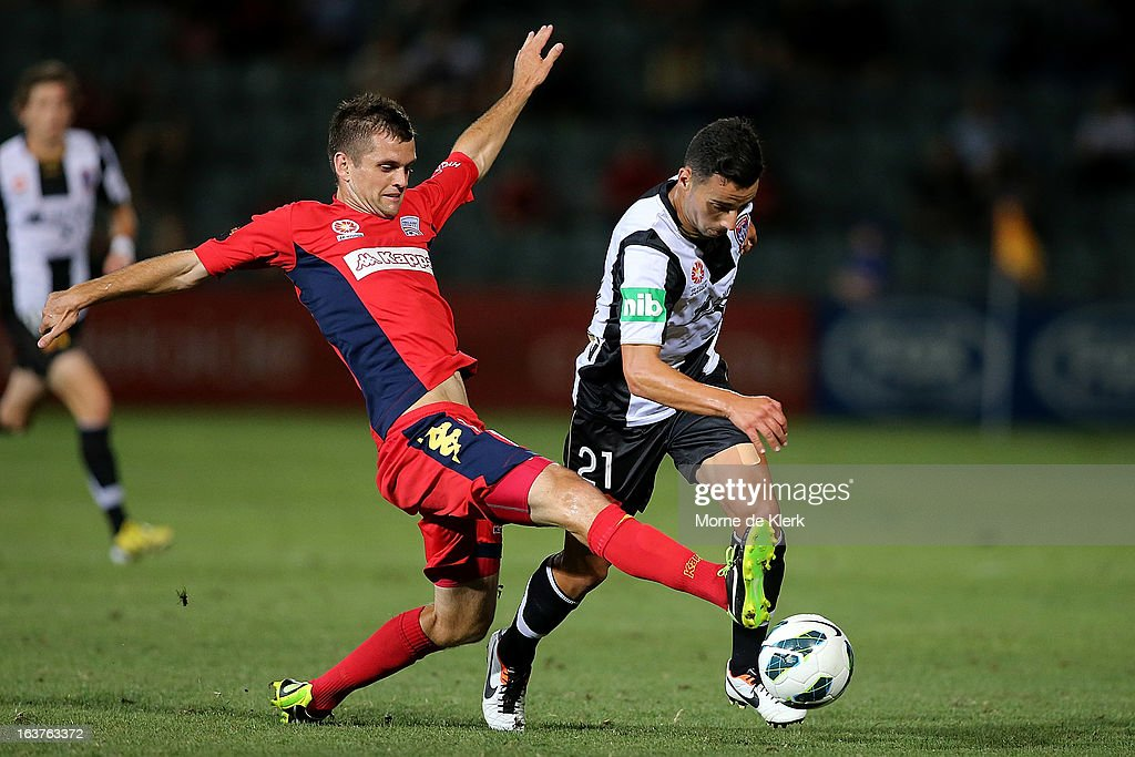 Cameron Watson of Adelaide tackles Marko Jesic of the Jets during the round 25 A-League match between Adelaide United and the Newcastle Jets at Hindmarsh Stadium on March 15, 2013 in Adelaide, Australia.