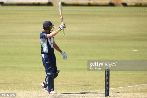 Cameron White of the Bushrangers raises hit bat to celebrate his 150 during the JLT One Day Cup match between Victoria and Tasmania at WACA on...