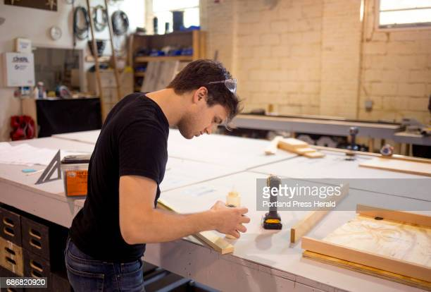 Cameron Wright builds a small platform for a show as he and other employees prepare for a busy season at the Maine State Music Theatre office in...