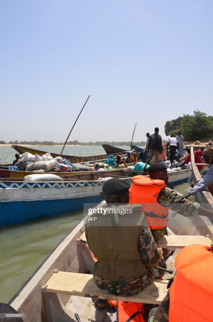 FORT -- Cameroon Marine captain Aboubakar (front of boat) arrives in Blangoua, near Lake Chad on March 1, 2013. More and more security forces say it is probable that Nigerian Islamist extremist group Boko Haram, who claimed responsibility for the kidnapping of a French family on February 19 in northern Cameroon, have moved north towards Chad. 'What I want, its to catch the bastards' Marine captain and head of the Cameroonian Marine presence on Lake Chad Aboubakar said. Lake Chad, a huge area with small islands and canals separating it from Cameroon, Nigeria, Chad and Niger, is a possible hiding place for the kidnappers of the French family and their hostages. AFP PHOTO/PATRICK FORT