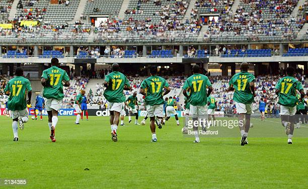 Cameroon players all warm with MarcVivien Foe shirts on to celebrate the life of a teammate who tragically died on the pitch in the semifinal before...