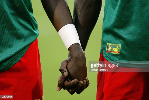 Cameroon players hold hands before the Confederations Cup Group B match between USA and Cameroon on June 23 2003 at the Stade Gerland in Lyon France...