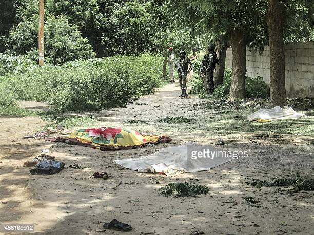 Cameroon security forces look on while a victim of a twin suicide attack lies on the ground in the extreme north village of Kolofata on September 13...