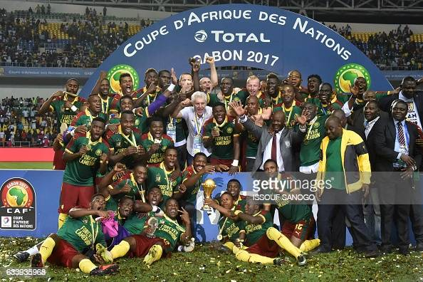 Cameroon team players and Cameroon's Belgian coach Hugo Broos celebrate with the winner's trophy after beating Egypt 21 to win the 2017 Africa Cup of...