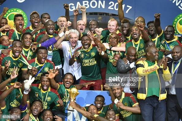 TOPSHOT Cameroon team players and Cameroon's Belgian coach Hugo Broos celebrate with the winner's trophy after beating Egypt 21 to win the 2017...