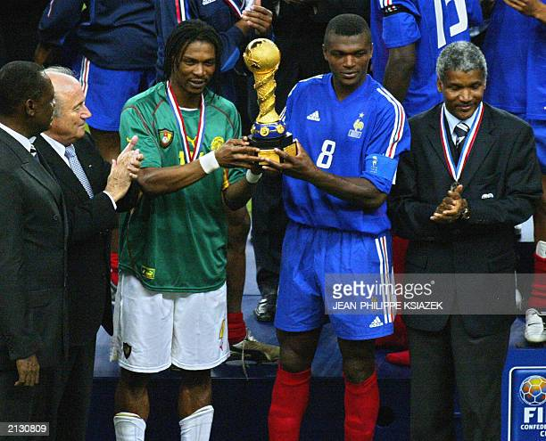 Cameroonian captain Rigobert Song and French captain Marcel Desailly hold the trophy next to Cameroonian President of soccer federation at the end of...