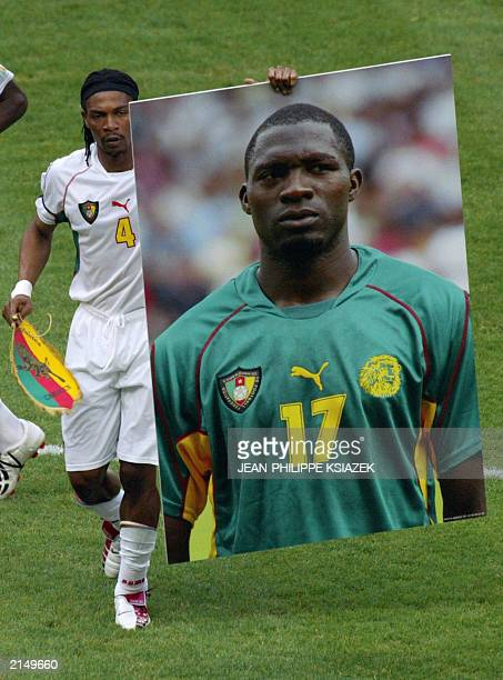 Cameroonian defender and captain Rigobert Song hold the picture of Marc Vivien Foe who died 26 June 2003 during the semi final match against Colombia...