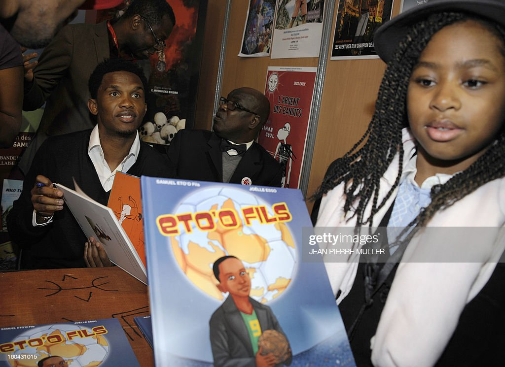 Cameroonian footballer Samuel Eto'o (L) signs a comic book about his life during the Comic book festival of Angouleme on January 31, 2013 which opened today. MULLER