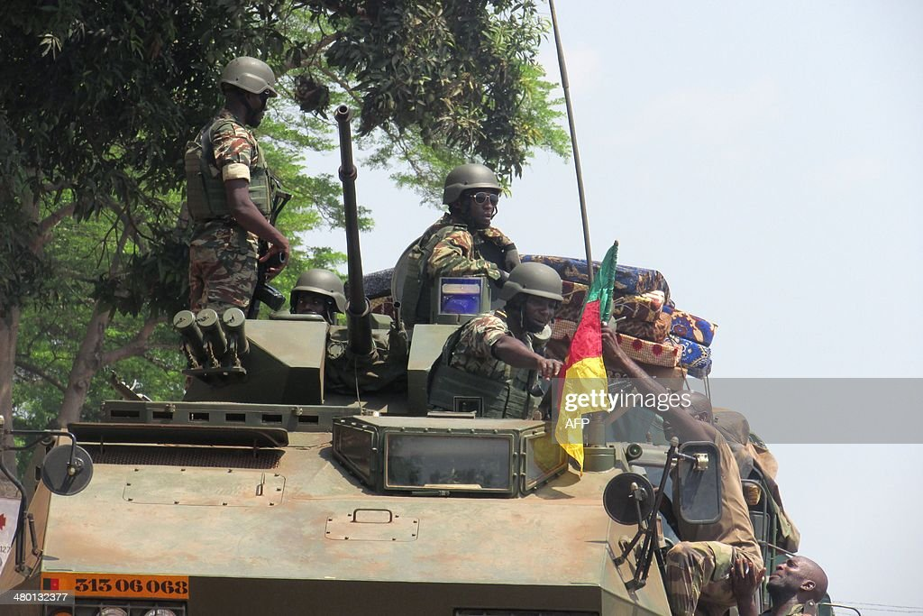 A Cameroonian soldier of the African-led International Support Mission to the Central African Republic (MISCA) hands a Cameroonian flag to another soldier sitting in an armoured vehicle as they patrol in the PK5 district of Bangui after an attack by anti-Balaka Christian militiamen on March 22, 2014. The UN's rights chief on March 20 expressed horror at the level of violence in the Central African Republic, citing cannibalism, child decapitations and gruesome lynchings. The chronically unstable country sank into chaos when rebels who had helped topple president Francois Bozize a year ago went rogue. The ensuing campaign of killing, raping and looting by the mainly Muslim former rebels prompted members of the Christian majority to form vigilantes known as 'anti-balaka' (anti-machete).