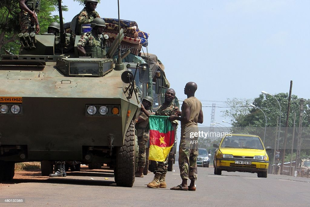 A Cameroonian soldier of the African-led International Support Mission to the Central African Republic (MISCA) holds a Cameroonian flag next to an armoured vehicle as the soldiers patrol in the PK5 district of Bangui after an attack by anti-Balaka Christian militiamen on March 22, 2014. The UN's rights chief on March 20 expressed horror at the level of violence in the Central African Republic, citing cannibalism, child decapitations and gruesome lynchings. The chronically unstable country sank into chaos when rebels who had helped topple president Francois Bozize a year ago went rogue. The ensuing campaign of killing, raping and looting by the mainly Muslim former rebels prompted members of the Christian majority to form vigilantes known as 'anti-balaka' (anti-machete).