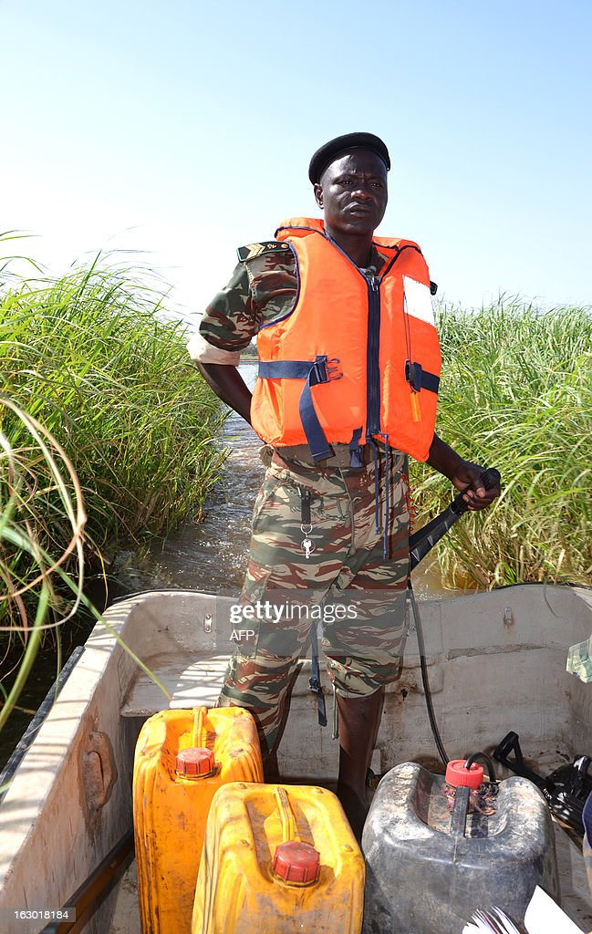 Cameroonian soldier patrols Lake Chad on March 1, 2013 near Darak close to the Nigerian border. Several security sources believe it is likely that members of the Islamist group Boko Haram, who have claimed responsibility in the kidnapping on February 19, 2013 of the French family in northern Cameroon and fled to Nigeria, then went north towards Lake Chad.