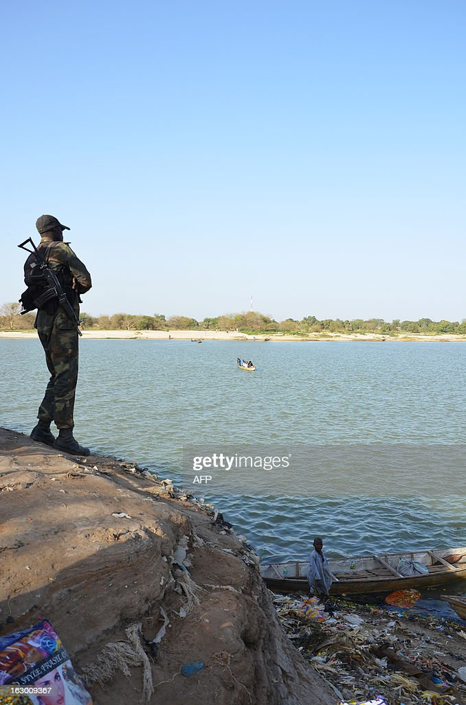 Cameroonian soldier standing on the banks of Lake Chad looks at the horizon towards Chad on March 1, 2013 in Blangoua. Several security sources believe it is likely that members of the Islamist group Boko Haram, who have claimed responsibility in the February 19, 2013 kidnapping of the French family in northern Cameroon and fled to Nigeria, have gone north towards Lake Chad.