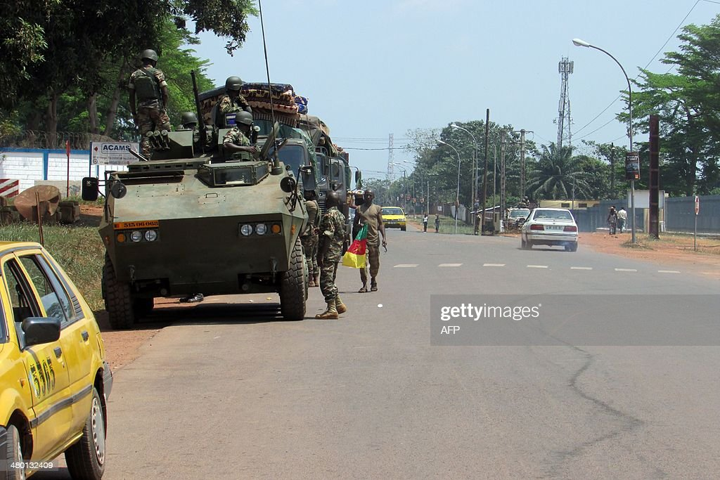 A Cameroonian soldiers of the African-led International Support Mission to the Central African Republic (MISCA) holds a Cameroonian flag next to an armoured vehicle as the soldiers patrol in the PK5 district of Bangui after an attack by anti-Balaka Christian militiamen on March 22, 2014. The UN's rights chief on March 20 expressed horror at the level of violence in the Central African Republic, citing cannibalism, child decapitations and gruesome lynchings. The chronically unstable country sank into chaos when rebels who had helped topple president Francois Bozize a year ago went rogue. The ensuing campaign of killing, raping and looting by the mainly Muslim former rebels prompted members of the Christian majority to form vigilantes known as 'anti-balaka' (anti-machete).