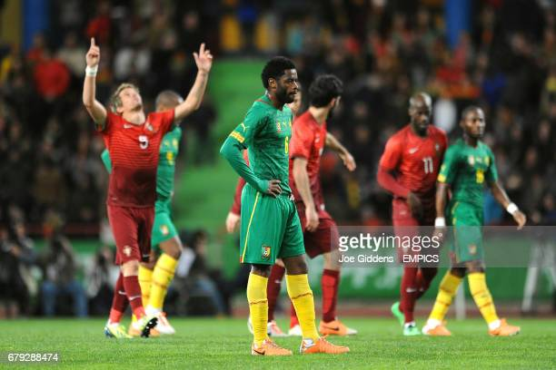 Cameroon's Alex Song stands dejected as Portugal's Fabio Coentrao celebrates his goal