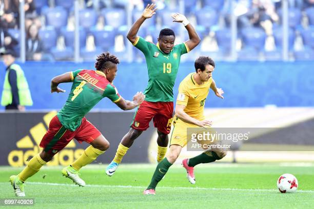 TOPSHOT Cameroon's defender Adolphe Teikeu and Cameroon's defender Collins Fai vie for the ball against Australia's forward Robbie Kruse during the...
