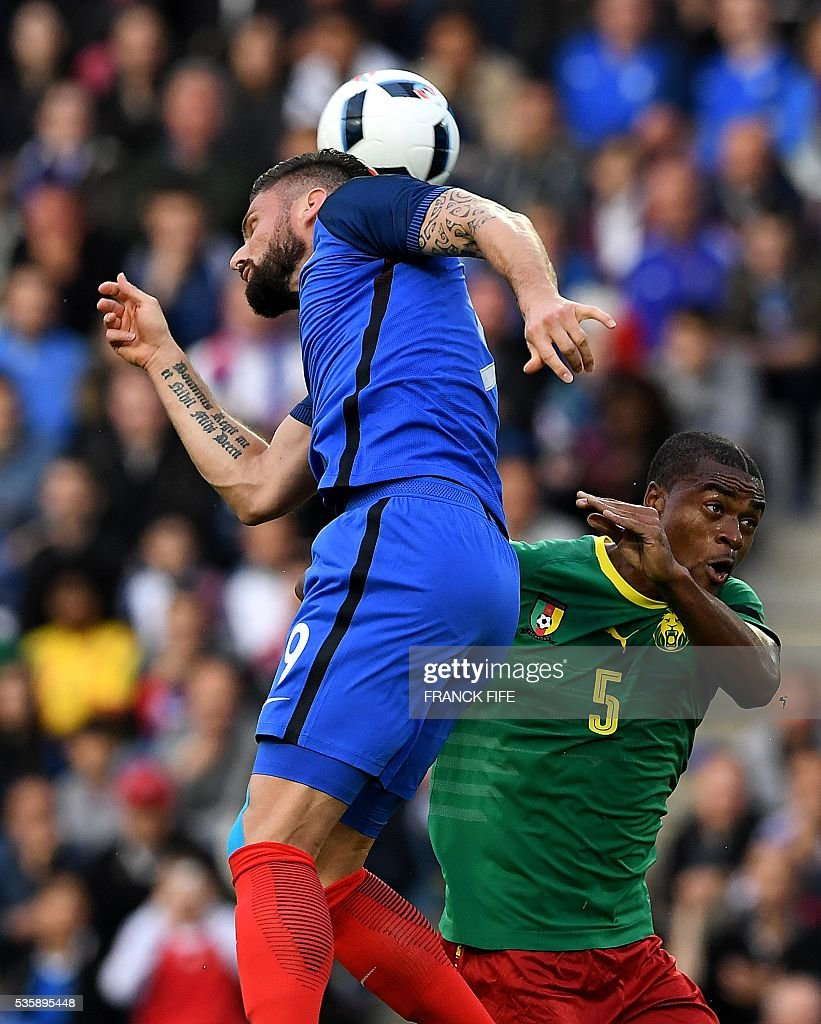Cameroon's defender Adolphe Teikeu (R) and France's forward Olivier jump for the head for the ball during the friendly football match between France and Cameroon, at the Beaujoire Stadium in Nantes, western France, on May 30, 2016. / AFP / FRANCK