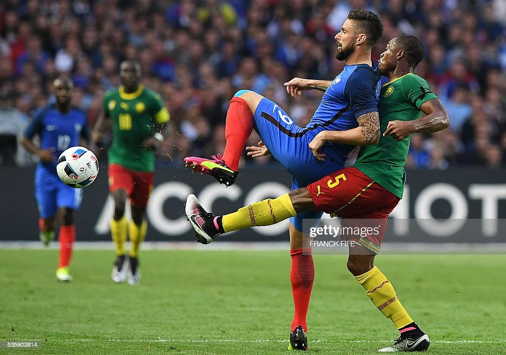 Cameroon's defender Adolphe Teikeu (R) fights for the ball with France's forward Olivier Giroud during the International friendly football match between France and Cameroon at the Beaujoire stadium, in Nantes, western France, on May 30, 2016 as part of the French team's preparation for the upcoming Euro 2016 European football championships. / AFP / FRANCK