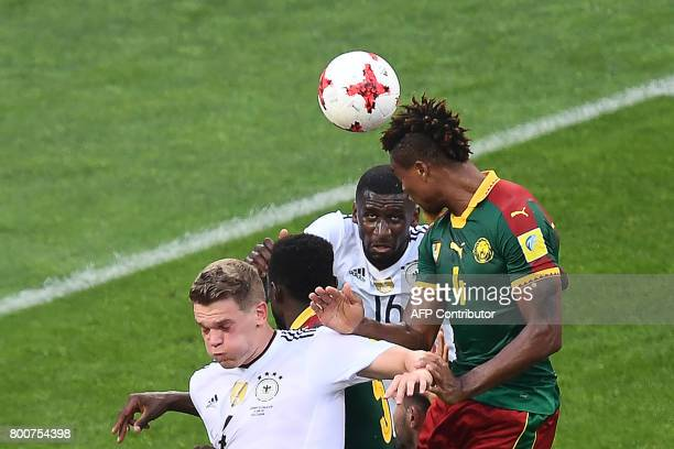 TOPSHOT Cameroon's defender Adolphe Teikeu heads the ball next to Germany's defender Antonio Ruediger and Germany's defender Matthias Ginter during...