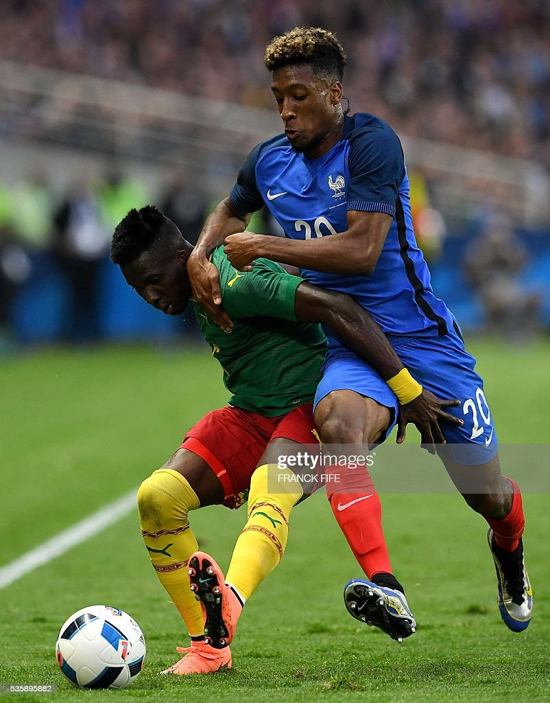 Cameroon's defender Ambroise Oyongo Bitolo (L) fights for the ball with France's forward Kingsley Coman (R) during the International friendly football match between France and Cameroon at the Beaujoire stadium, in Nantes, western France, on May 30, 2016 as part of the French team's preparation for the upcoming Euro 2016 European football championships. / AFP / FRANCK