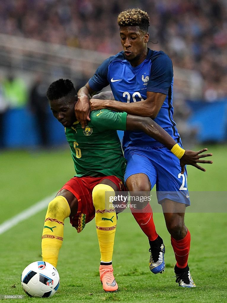 Cameroon's defender Ambroise Oyongo Bitolo (L) vies with France's forward Kingsley Coman during the friendly football match between France and Cameroon, at the Beaujoire Stadium in Nantes, western France, on May 30, 2016. / AFP / FRANCK