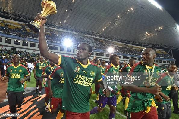 TOPSHOT Cameroon's defender Michael NgadeuNgadjui holds up the trophy as the team celebrates beating Egypt 21 to win the 2017 Africa Cup of Nations...
