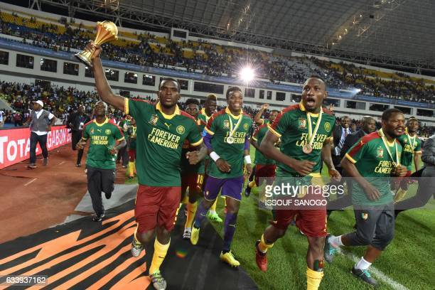 Cameroon's defender Michael NgadeuNgadjui holds up the trophy as the team celebrates beating Egypt 21 to win the 2017 Africa Cup of Nations final...
