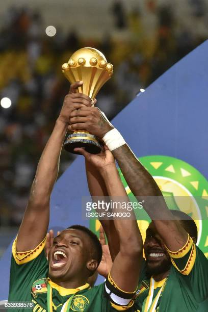 Cameroon's forward Benjamin Moukandjo and Cameroon's defender Nicolas Nkoulou hold up the winner's trophy as they celebrate beating Egypt 21 to win...
