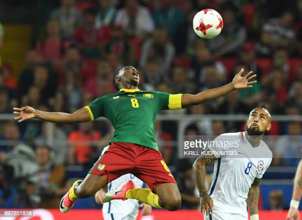 Cameroon's forward Benjamin Moukandjo reacts as he jumps to head the ball next to Chile's midfielder Arturo Vidal during the 2017 Confederations Cup...