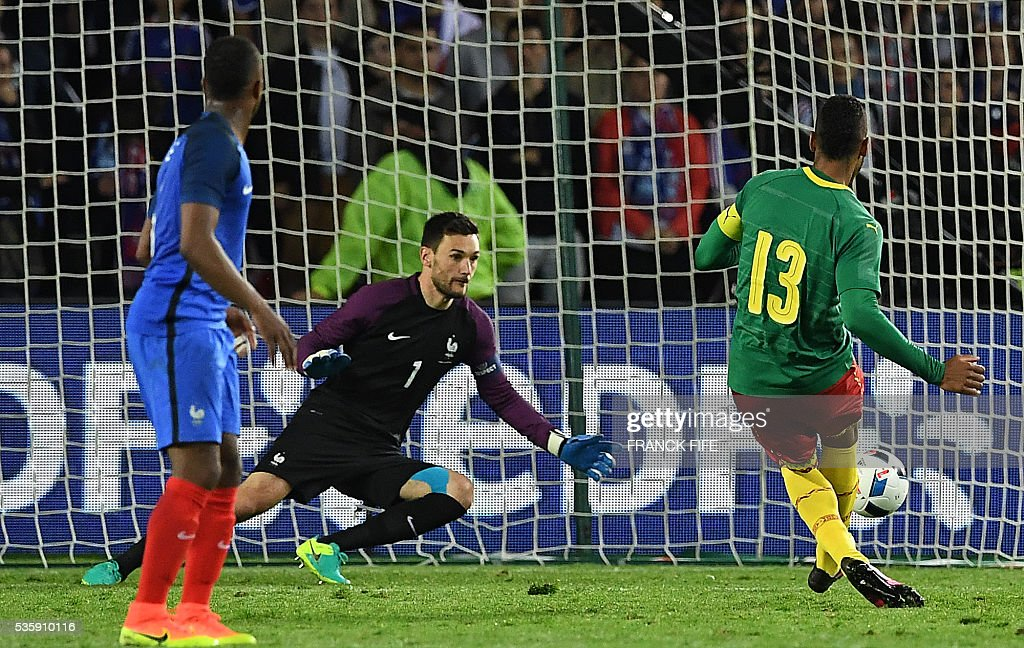 Cameroon's forward Eric Maxime Choupo Moting (R) scores a goal past France's goalkeeper Hugo Lloris (C) during the friendly football match between France and Cameroon, at the Beaujoire Stadium in Nantes, western France, on May 30, 2016. / AFP / FRANCK