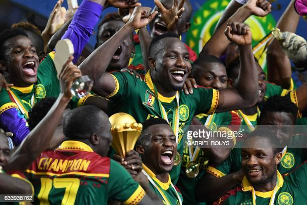 Cameroon's forward Jacques Zoua and forward Benjamin Moukandjo celebrate with other team members as they hold the winner's trophy after beating Egypt...