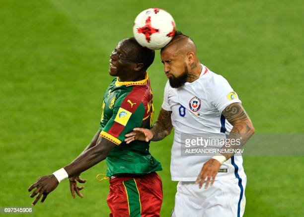 TOPSHOT Cameroon's forward Vincent Aboubakar heads the ball with Chile's midfielder Arturo Vidal during the 2017 Confederations Cup group B football...