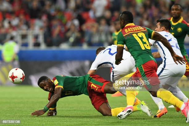 TOPSHOT Cameroon's midfielder Arnaud Djoum falls after being challenges by Chile's midfielder Marcelo Diaz and Chile's forward Edson Puch during the...