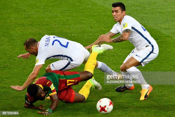 Cameroon's midfielder Arnaud Djoum falls as he challenges Chile's midfielder Marcelo Diaz and Chile's forward Edson Puch during the 2017...