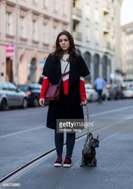 Camila Alvarez and her dog wearing a sleeveless wool coat white red sweater bordeaux Chanel bag denim jeans sneakers on March 26 2017 in Berlin...