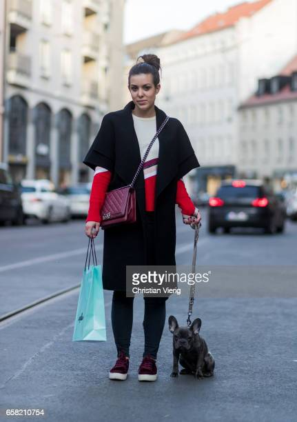 Camila Alvarez and her dog wearing a sleeveless wool coat white red sweater bordeaux Chanel bag denim jeans Douglas shopping bag sneakers on March 26...