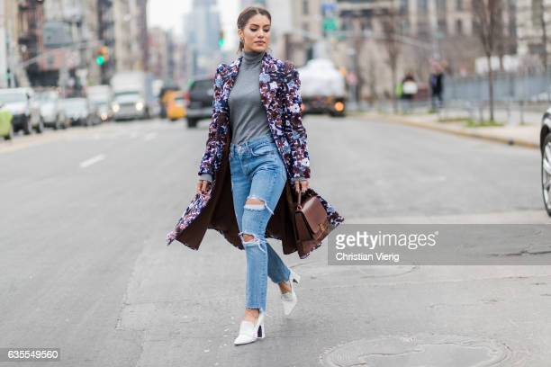 Camila Coelho wearing a coat with floral print ripped denim jeans outside Michael Kors on February 15 2017 in New York City
