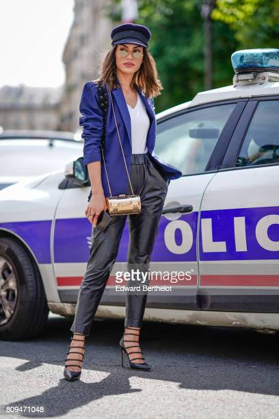 Camila Coelho wears a beret hat a blue blazer jacket a white top black leather pants black heels and a golden bag in front of a police car outside...