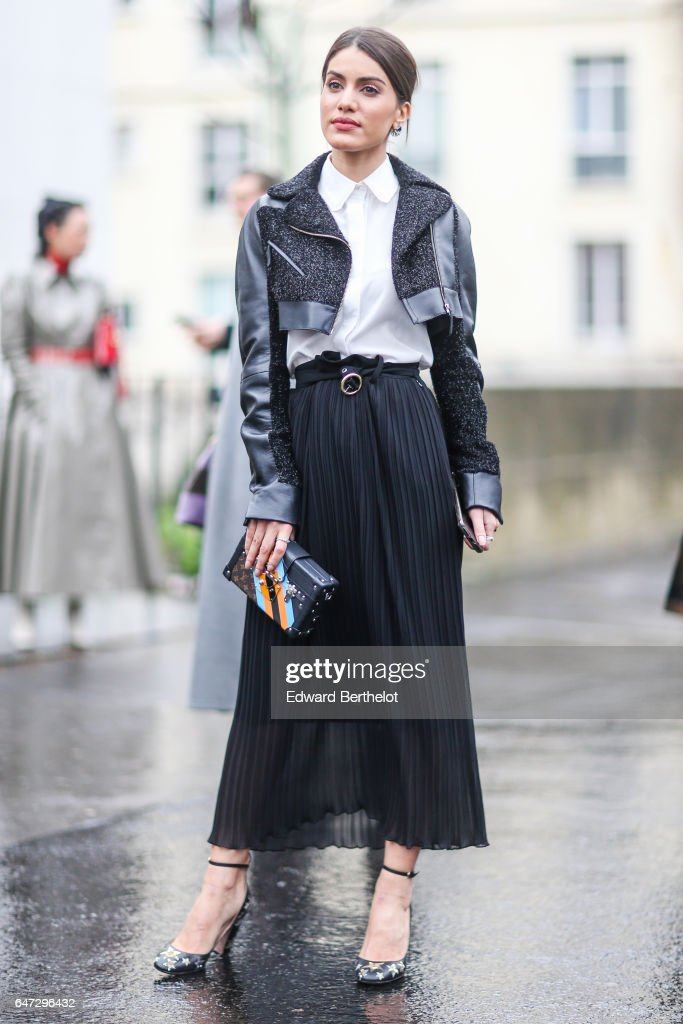Camila Coelho wears a jacket, a white top, and a black skirt, outside the Rochas show, during Paris Fashion Week Womenswear Fall/Winter 2017/2018, on March 1, 2017 in Paris, France.
